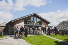 This is an image of our Green Room Bar. The building is clad in oak planks. It has a pitched roof and glazing at the front. It has bi-fold doors that are open. Guests are spilling out of the doors onto the lawn in front of the building. The sky behind is bright blue with some clouds. There is a granite chippin path leading up to the building to the left of the shot. Ther are aound 30 weddnig guests visible in the picture.