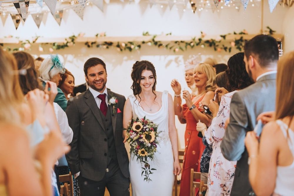 Amy and Kieran  leaving the weding barn hand in hand and smiling being cheered by their guests. Amy holds a bouquet of sunflowers