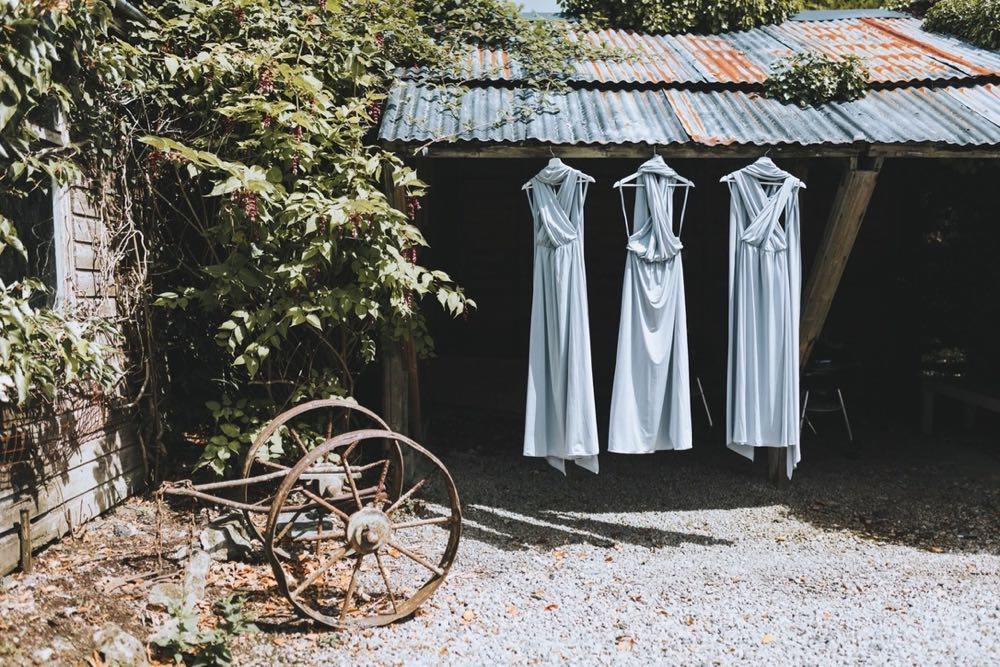 3 bridesmaids dresses hanging in the old wood shed