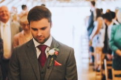 Kieran  waiting fro Amy to come down the aisle. Facing the camera and looking nervous
