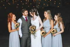 Amy and Kieran with their 3 bridemaids in pale blue dresses holding sunflower posies