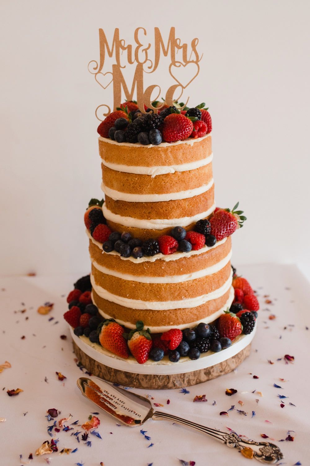 A close up shot of a naked sponge with 2 tiers each made up of 3 cream-filled layers. Each tier is decorated with berries.