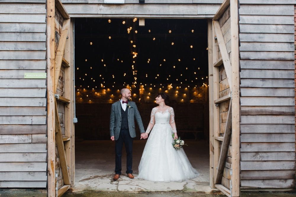 The couple are standing in the doorway of the Really Rustic Barn. The doors are open and they are about twice the height of the couple. You can see festoon lighting in the backgorund inside the barn. The are facing the camera and holding hands.  The bride has She has dark hair worn up. She has a fitted white dress with a sweatheart neckline and lace sleeves. The groom is wearing a tweed 3 piece suit and brown bow-tie.