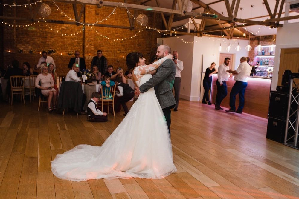 The couple are having their first dance in the Red Brick Barn. You can see some guests and a bar in the backgorund inside the barn. The are facing each other side on to the camera and embracing.  The bride has She has dark hair worn up. She has a fitted white dress with a sweatheart neckline and lace sleeves. The groom is wearing a tweed 3 piece suit and brown bow-tie.