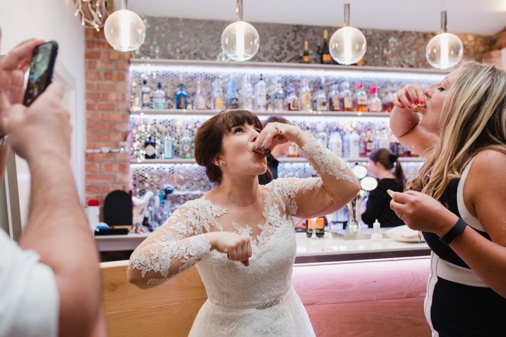 The bride is downing a shot  in the Red Brick Barn. You can see some guests and a bar in the backgorund inside the barn. She is facing the camera.  The bride has She has dark hair worn up. She has a fitted white dress with a sweatheart neckline and lace sleeves and a full skirt..