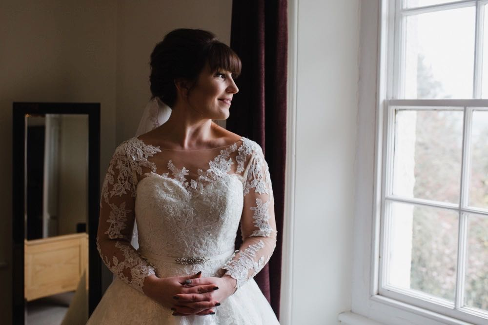 A bride faces the camera, her head is turned to lookout of a window to her left. She has dark hair worn up. She has a fitted white dress with a sweatheart neckline and lace sleeves