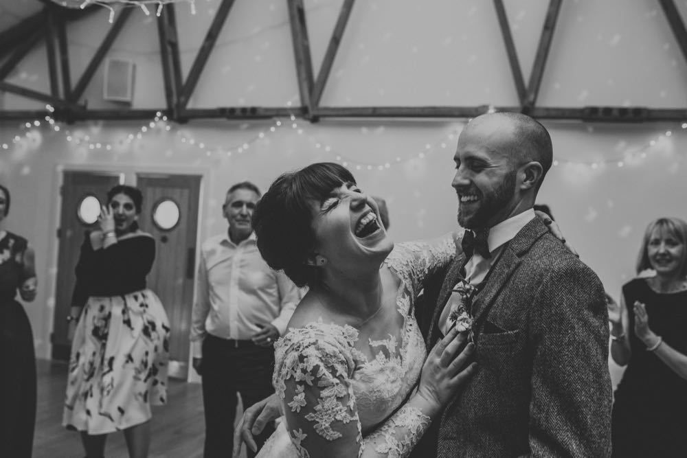 The couple are dancing in the Red Brick Barn. You can see some guests and in the backgorund inside the barn. The are facing each other side on to the camera and embracing.  The bride has She has dark hair worn up. She has a fitted white dress with a sweatheart neckline and lace sleeves. The groom is wearing a tweed 3 piece suit and brown bow-tie.