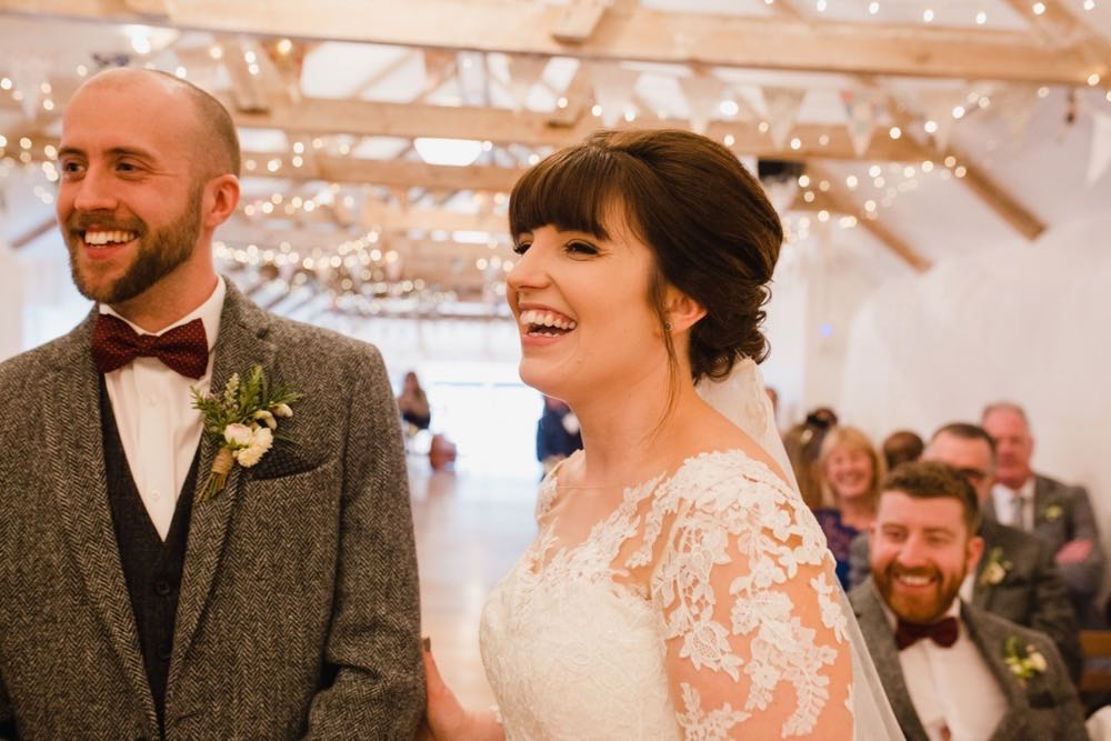 The bride and groom are facing the camera in the wedding barn during their ceremony. The bride has She has dark hair worn up. She has a fitted white dress with a sweatheart neckline and lace sleeves. The groom is wearing a tweed 3 piece suit and brown bow-tie.