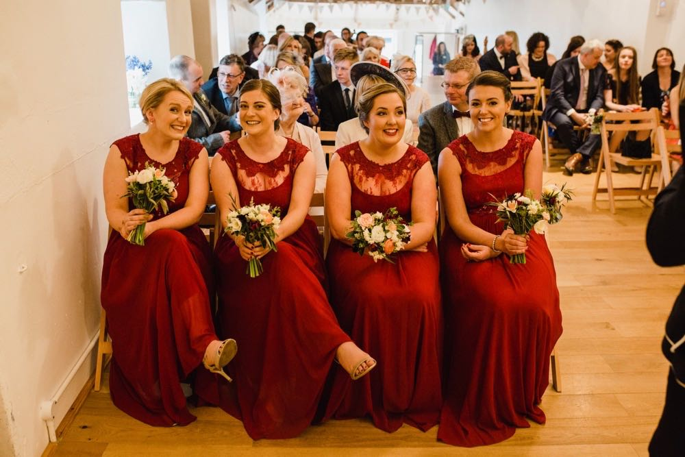A group of 4 bridesmaids are seated in the front row of the left hand column of chairs inthe wedding barn, they are waring re dresses and holding flowers
