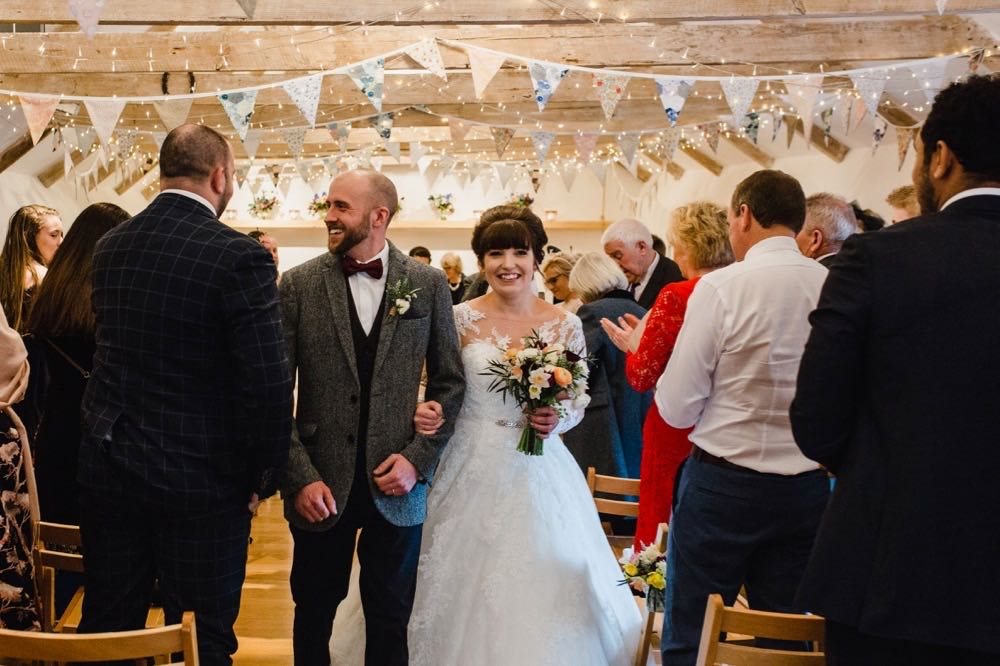 The bride and groom are walking out of the weddin barn holding hands after their ceremony. The bride has She has dark hair worn up. She has a fitted white dress with a sweatheart neckline and lace sleeves. The groom is wearing a tweed 3 piece suit and brown bow-tie.