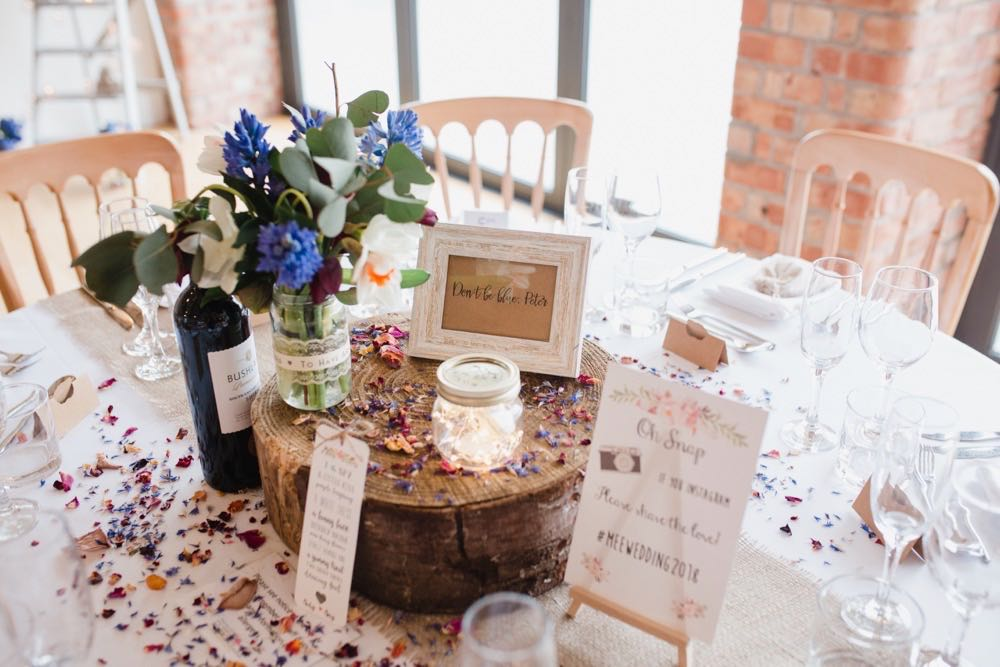 This picture shows a table centrepiece made up of a log slice, a candle in a lace jar, a table name and table confetti.