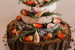 "TA close up shot of a ""cake of cheese' on a log slice decorated with rosemary and figs."