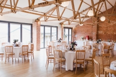 A picture showing the Red Brick barn set up for the wedding meal with round tables