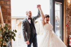 The bride and groom are walking into the Red Brick barn. They are holding hands and have their hands raised in celebraition. The bride has She has dark hair worn up. She has a fitted white dress with a sweatheart neckline and lace sleeves. The groom is wearing a tweed 3 piece suit and brown bow-tie.