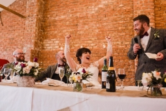 "The wedding party are at their places at a long ""top"" table in front of the Red Brick wall in the barn. The best man is on hos feet making a speech and the bride has her arms lifted in a cheer,"