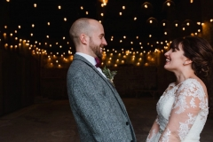 The couple are standing inside the Really Rustic Barn.  You can see festoon lighting in the backgorund inside the barn. The are facing each other and the shot is fromthe waist up.  The bride has She has dark hair worn up. She has a fitted white dress with a sweatheart neckline and lace sleeves. The groom is wearing a tweed 3 piece suit and brown bow-tie.