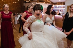 The bride is dancing and swirling her skirt  in the Red Brick Barn. You can see some bridesmaids and a bar in the backgorund inside the barn. She is facing the camera and smiling broadly.  The bride has She has dark hair worn up. She has a fitted white dress with a sweatheart neckline and lace sleeves and a full skirt..
