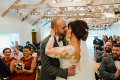 The bride and groom are facing each other and embacing in the wedding barn during their ceremony. The bride has She has dark hair worn up. She has a fitted white dress with a sweatheart neckline and lace sleeves. The groom is wearing a tweed 3 piece suit and brown bow-tie.