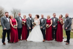 An informal group shot of the bride and groom and their 4 bridesmaids and groomsmen. The bridesmaids they are wearing red dresses and holding flowers. The bride has dark hair worn up. She has a fitted white dress with a sweatheart neckline, lace sleeves and a full skirt. The groom is wearing a tweed 3 piece suit and brown bow-tie. the groomsmen are dressed like the groom.