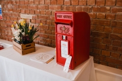 There is a white clothed table in this picture with a red brck wall in the background. On the table is a red post box (used for cards). There is also a box of flowers.