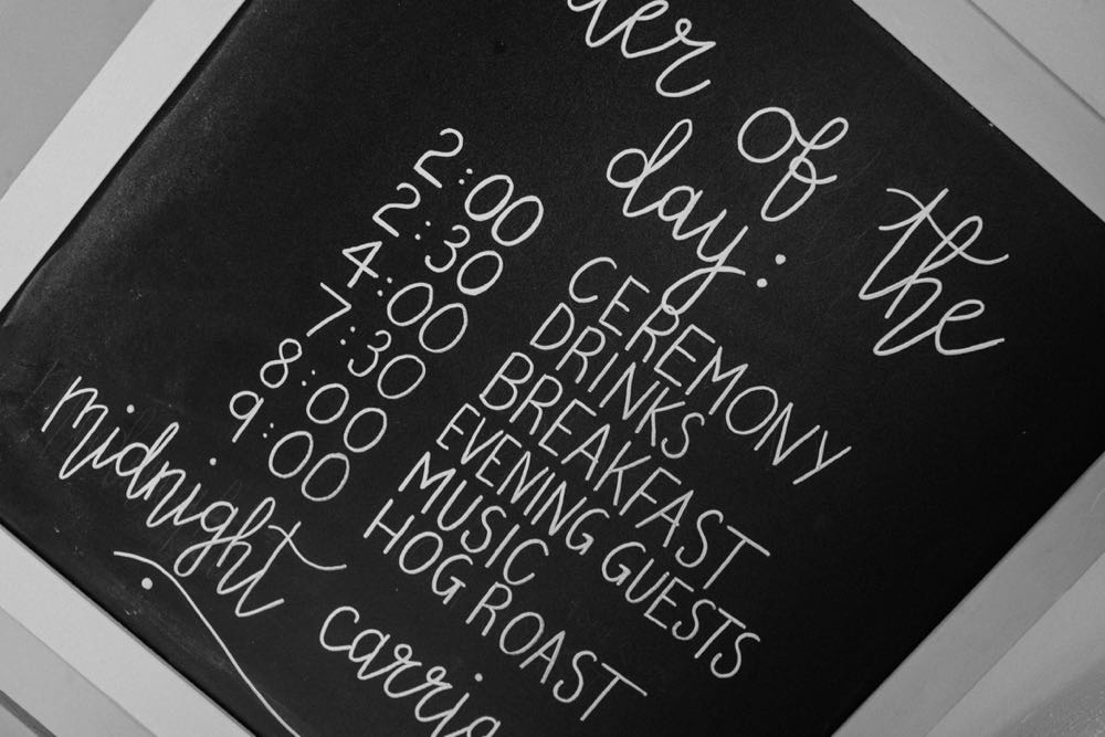"A cloe up picture of a blackboard sign with white writting with ""order of the day\"". Ceremony, drinks, Breakfast, evening guests, music, hogroast"
