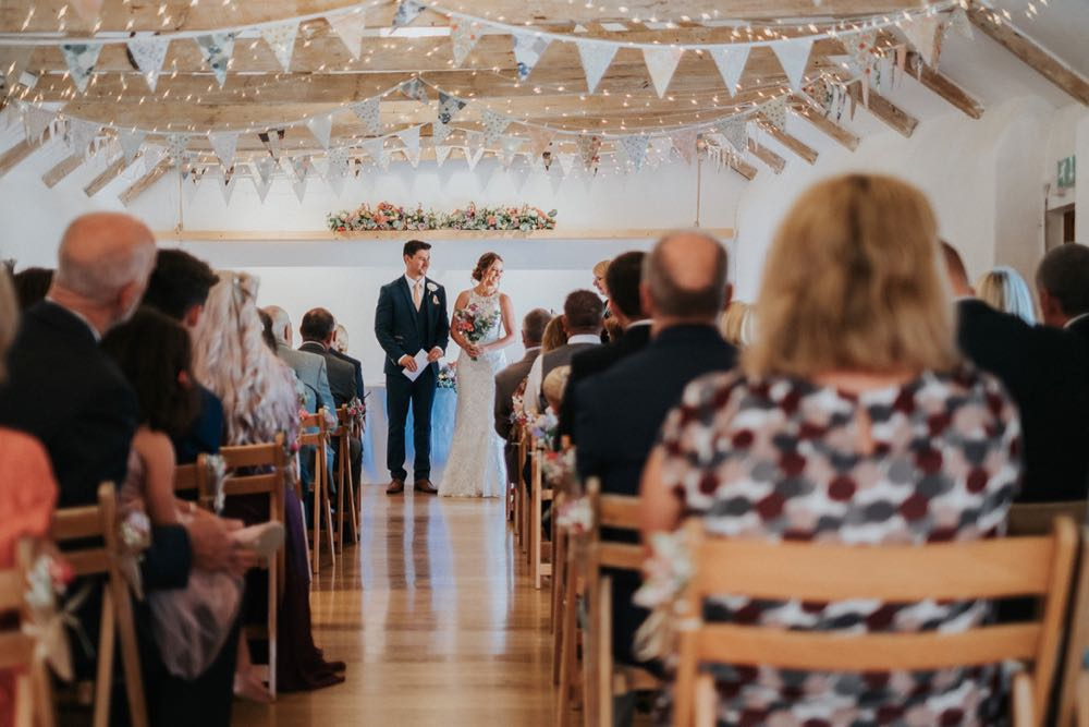 This picture is taken from the entrance end of the wedding barn. The guests  are seated in 2 columns of folding wooden chairs and they have their back to the camera.. At the other end of the barn, in the distance you can see the bride and groom. She is wearing a full length white gown and the groom is wearing  a dark suit. You can see the A frame beams inthe wedding barn roof with bunting strung across and the oak floor inthe aisle.