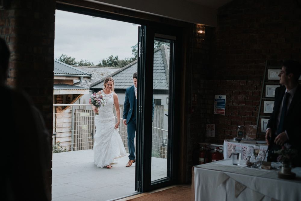 This black and white photo shows the couple framed in the doorway to the Red Brick Barn. They are about to enter the Red Brick Barn to join their guests for the wedding breakfast