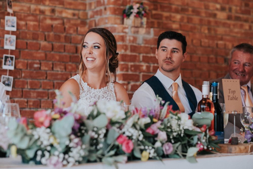 This picture shows the couple sitting on the top table during the wedding breakfast. The top table is set up in front of the red brick wall. the bride is on the right and the groom is on the left. The foreground is full of flowers.