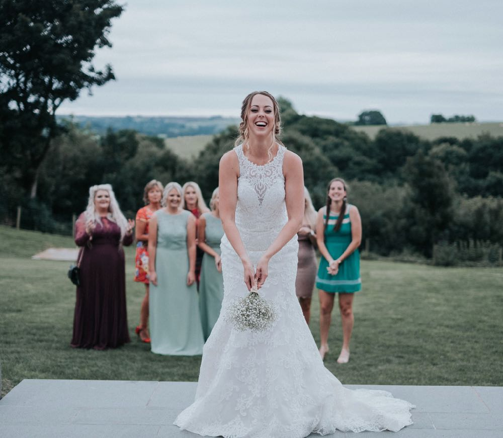 The bride is standing in the foreground facing the camera. She is wearing a white, sleeveless  gown with a high neck and lace details. Behind her onthe lawn there is a group of girls standing on a lawn who are waiting for the bride to throw her bouquet. In the background you can see trees and rolling hills. The lawns are parched giving the feeling that it is the height of summer.