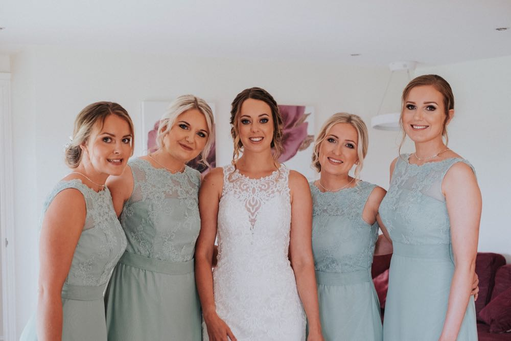 The bride is standing in her wedding dress flanked by 4 bridesmaids, 2 on each side of her. The bride is wearing a white sleevless gown with a high neck and lace details. The bridesmaids are waering gray dresses of a similar style. The photo is taken indoors.