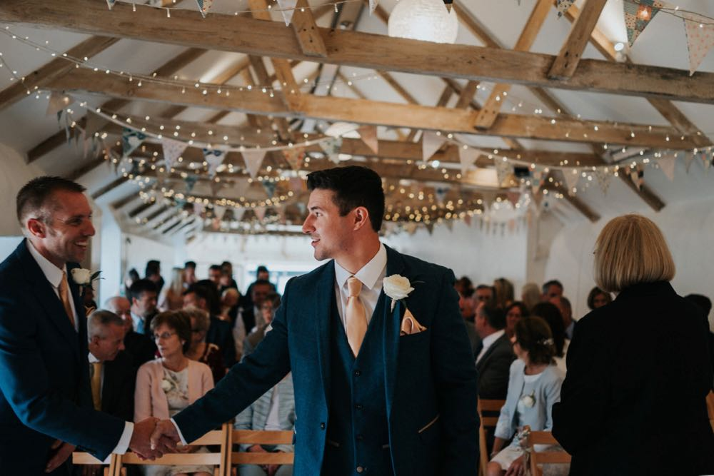 The groom is standing at the front (ceremony end) of the wedding barn. He as his back to the guests who are seated in 2 columns of folding wooden chairs behind him.  He is wearing a navy suit, white shirt and light coloured tie. He has a white flower in his left lapel. He is turning slightly to his right to shake hands with another man. The registrar is on his left and has her back to the camera. You can see all the A-frame roof beams of the weddin barn/