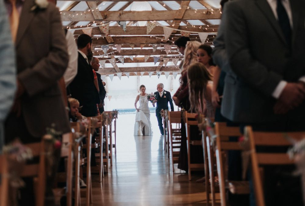 This picture is taken from the ceremony end of the wedding barn. The guests  are seated in 2 columns of folding wooden chairs. At the other end of the barn, in the distance you can see the bride coming into the barn escorted by her father. She is wearing a full length white gown and her faher is wearing a dark suit. You can see the a frame beams inthe wedding barn roof and the oak floor inthe aisle.