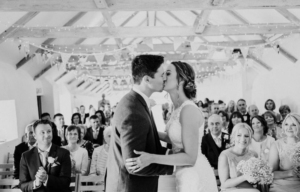 This black and white picture is taken from the ceremony end of the wedding barn. The guests  are seated in 2 columns of folding wooden chairs and they are facing the camera in the background. In the foreground facing the camera you can see the bride and groom. She is wearing a white, sleeveless  gown with a high neck and lace details. The groom is wearing  a dark suit, white shirt and light coloured tie. He has a white flower in his left lapel. The couple are standing side by side with the bride on the right and the groom on the left. They are facing each other and kissing. You can see the A frame beams inthe wedding barn roof with bunting strung across and the oak floor inthe aisle.