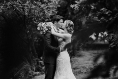 This black and white picture is taken outdoors. In the foreground facing each other and embracing you can see the bride and groom. She is wearing a white, sleeveless  gown with a high neck and lace details. She has a bouquet in her hand. The groom is wearing  a dark suit,  The couple are standing with the bride on the right and the groom on the left. They are facing each other and kissing. You can see lots of trees and bushes in the background.