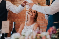 This is a close up of the bride smiling during the meal. You can see twi arms raised ina toast and she has her head thrown back and is laughing