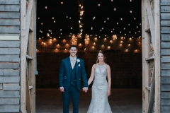 This picture is taken outside the really rustic barn. In the foreground facing the camera you can see the bride and groom. She is wearing a white, sleeveless  gown with a high neck and lace details. The groom is wearing  a dark suit, white shirt and light coloured tie. He has a white flower in his left lapel. The couple are standing side by side holding hands with the bride on the right and the groom on the left. tThe coule are facing the camera. You can see the festoon lighting in the really rustic barn ceiling.