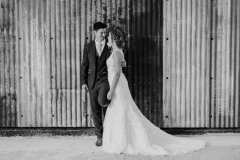 This black and white picture is taken in the Really Rustic Barns. It is a full length shot of the couple. She is wearing a white, sleeveless  gown with a high neck and lace details. The groom is wearing  a dark suit,  The couple are standing with the bride on the right and the groom on the left. They are facing each other.
