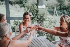 The bride surrounded by her 3 brodesmaids enjoys a drink on the patio. The four girls are seated and are clinking glasses with glasses raised. The bride is in the middle of the group.
