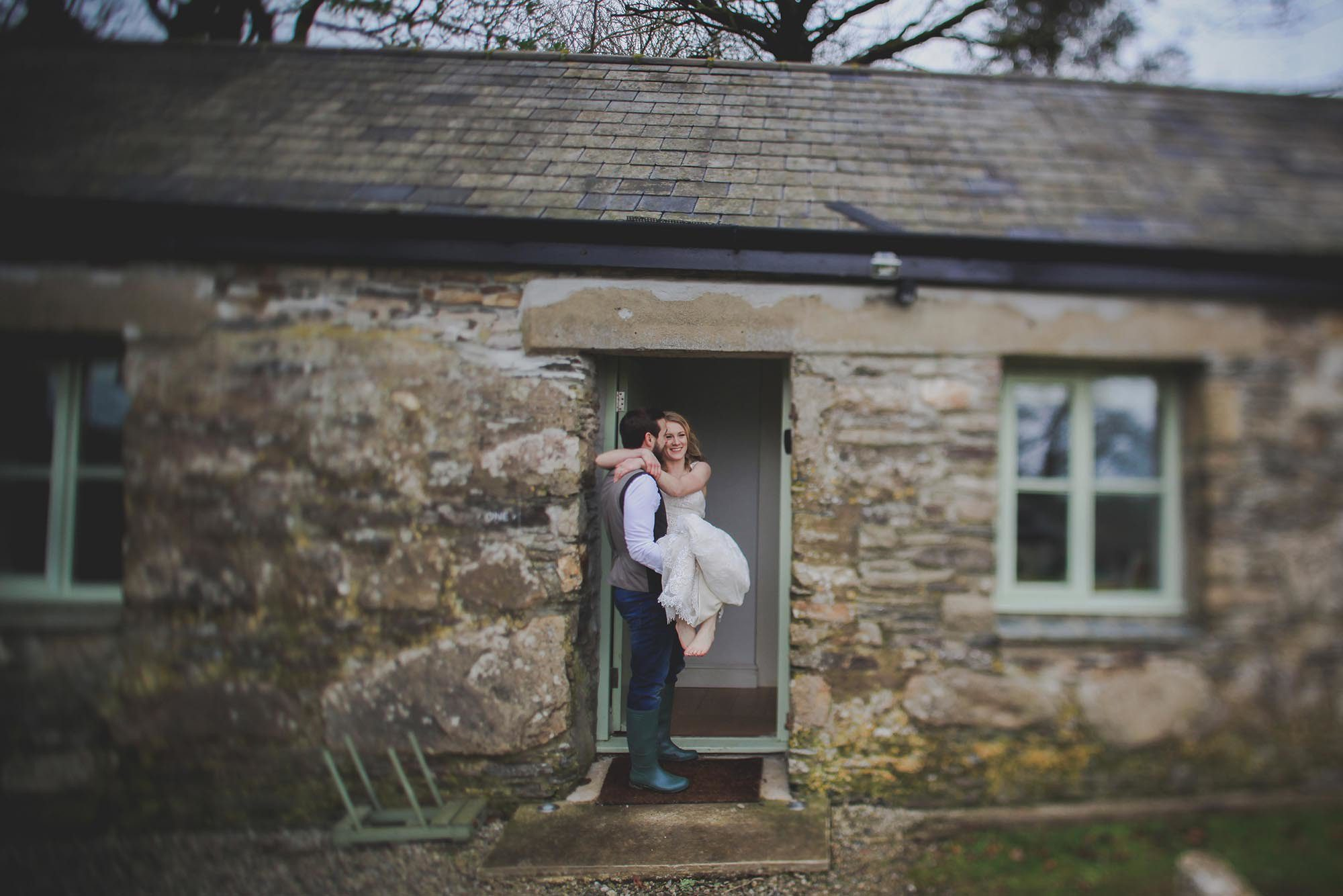 This is a photo of a groom carrying his bride over the threshold into cottage number 1. The groom is on the left, side on to the camera and the bride is on the right seated in the grrom's arms facing the camera. The groom has dar hair and is wearing dark trousers, a brown tweed waistcoat and a white shirt. He has a beard and is weraing green wellies. The brode is wearing a short-sleeved, full length white dress. She has light brown hair that she is wearing loose and her feet are bare. Cottage number one sleeps two people. The proerty is single storey. The photo shows part of the width of the cottage. In the background you can see trees which are bare. The cottage is made of granite stone and is brown and grey in colour. The roof is constructed of grey slate and is pitched with the roof line running from left to right of the photograph along the length of the cottage. The door is in the middle of the cottage and is painted pale green and is open. On either side of the door you can see a window. They are 4 pane casement style windows and are also painted pale green. On the left hand side of the door you can seee a 4 spoke welly rack painted pale green.