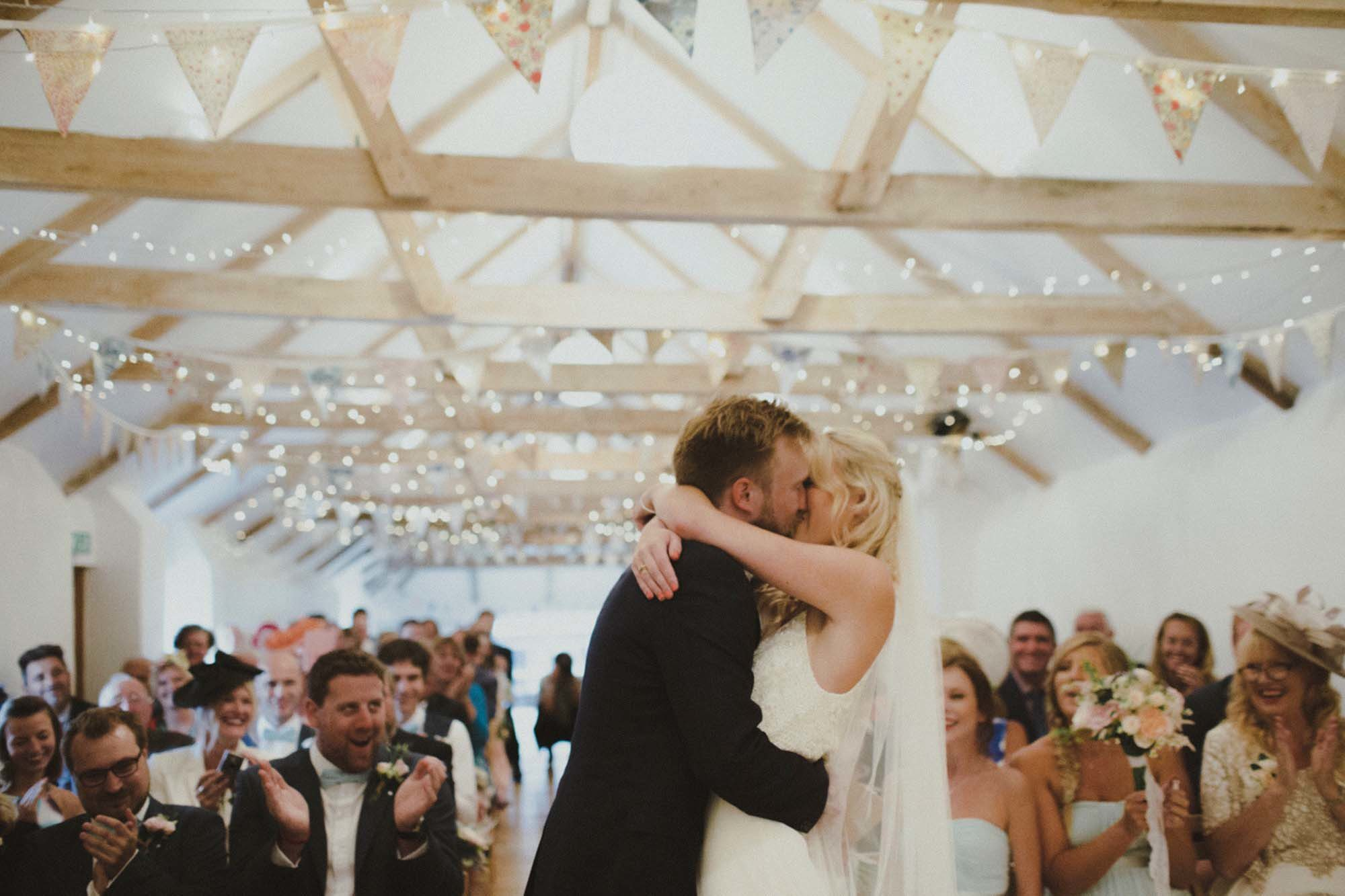 "This photo shows the ""you may kiss the bride"" moment of a ceremony held in the wedding barn. In the foreground you can see the bride and groom having a kiss. The guests are seated behind the couple in two columns of rows of chairs. The wedding barn has an oak floor and the walls and ceiling are painted white. There is a vaulted ceiling with a sets of old, oak, a-frame beams supporting the roof. You can see 10 sets of the beams in the image. There are fairy lights garlanding the beams and there is bunting on the beams too. the guests are seated and are looking at the bride and groom and clapping. The groom is wearing a dark jacket and has light brown hair and a beard. The bride is wearing a lace, sleeveless dress and has blond hair worn loose. She is wearing a veil."