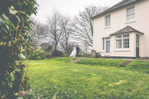 This is a picture of a bride and groom beside the farmhouse. The bride and groom are in the distance in the middle of the photo. The bottom half of the image is lawn. On the left there are some camellia bushes in the foreground. In the background there are some trees without any leaves. The farmhouse takes up the top, right hand quadrant of the image. Only part of the framhouse is in the shot. The farmhouse is rendered and painted white. It has a gray slate roof. The windows are georgian style sash windows and are painted white. There are two windows on the first floor and a French door on the ground floor. There is a porch with two sets of Georgian windows and a pitched slate roof. On the right hand side of the porch there is a black half-glazed door. There is a slight rise up towards the house and there is a small set of three steps on the left and a small step for three steps on the right of this ridge. The bride and groom are standing at the top of the steps on the left hand side of the house. The bride is wearing a white full gown with long sleeves. The groom is wearing a dark suit. There are some camellia petals on the lawn from the bushes indicating that the picture is taken in early spring.