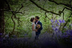 Newly weds kissing in a bluebell woodland