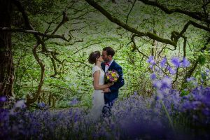 Newly weds kissing in a bluebell wood. The couple are in the centre of the image. They are surrounded by trees in leaf and there are lots of bluebells in the foreground. The image is taken in springtime. The couple are kissing the bride is on the left of the photo and the groom is on the right. The bride is wearing a lacy sleeveless dress you cannot see the couple's feet. In her right hand the bride is holding a bouquet of bright pink and bright yellow flowers. She has dark hair and she wears it up. The groom is wearing a mid blue suit with a white shirt and red bowtie. The groom has dark hair and a beard. The bride also has dark hair.