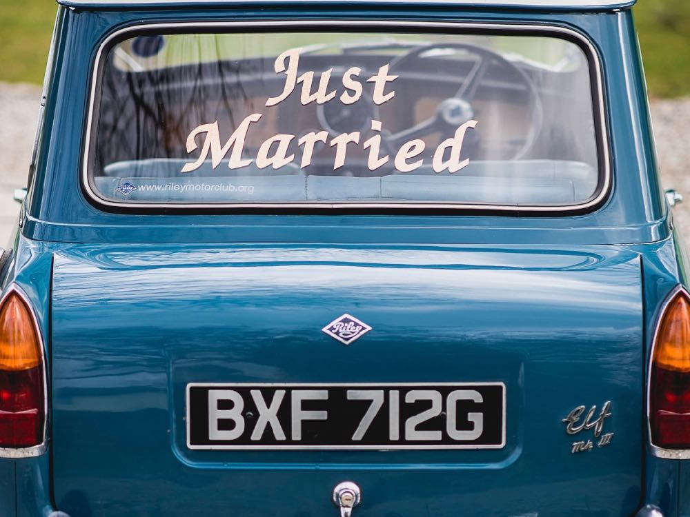 This image shows the rear of a Riley Elf car. It is a close-up shot of the back of the car and there is a saying in white writing on the rear window saying just married. Riley elf is blue in colour and the registration number is VXF712G.