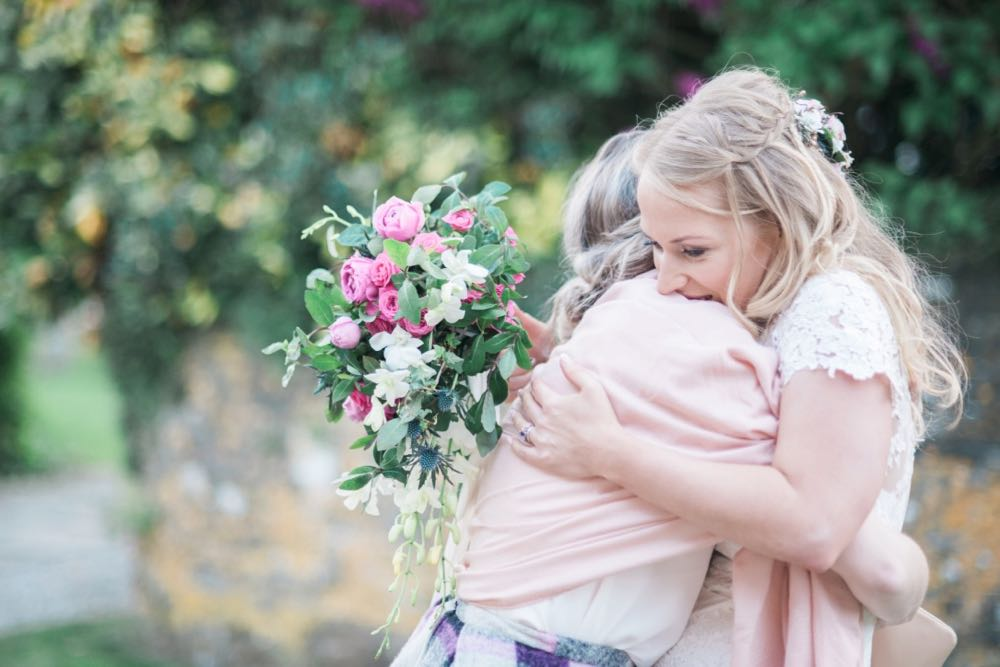 Image shows a bride hugging one of her guests. The bride is on the right and the guests is on the left. The bride has blond hair worn loose it is clipped at the back with a flower decoration. Her dress has short lace sleeves. The guest she is hugging is wearing a purple patterned skirt, white blouse and a pink stole. She also has blond hair which she is wearing up. In her right hand the bride is holding a bouquet of green foliage, pink roses and white flowers. In the background there is a Cornish stone wall made of granite which is brown and gray. There are also some bushes and shrubs in the background.