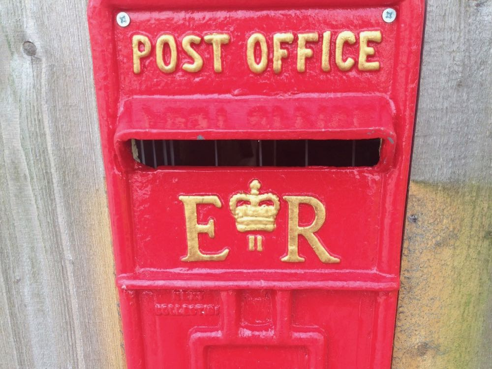 "This image shows a wall-mounted traditional, metal, post-office postbox. It is red in colour with gold lettering. At the top it says ""post office"" and under the posting slot it says ""E R"". Between the E and the R there is a crown motif and a number 2. The postbox is mounted on a wooden wall."