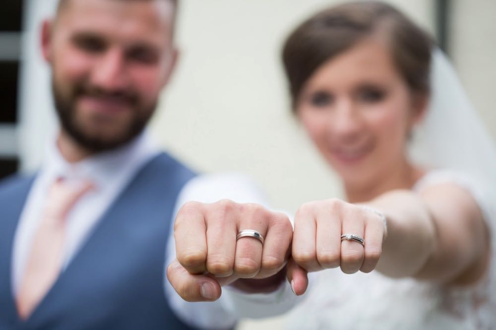 This shot shows a bride and groom with their fists clenched showing off their wedding rings. The couple's fists are in focus and they are punching towards the camera. Their faces are blurred. The groom is on the left and the bride is on the right. The groom has dark here has a beard. he is wearing a mid-blue waistcoat, a white shirt and a pink tie. The bride is wearing a white dress with short sleeves and lace details and is wearing a veil. The image shows the couple from the chest up.