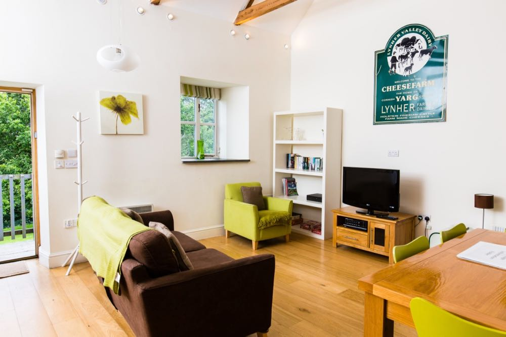 This is an image of the lounge area of cottage number three which is a sleeps 4 cottage. The room has oak flooring. The front door can be seen and the door is open. OUtside the door you can see some wooden ballustrades and green trees in leaf. The walls are all painted cream. At the top of the wall you can just see the edge of the a-frame beams that support the roof. There are spotlights around the edge of the ceiling. There is a pendant light hanging to the right of the door. There is one window which is a casement style four pane window with a striped blind that is open. Out of the window you can see more trees. There is a slate windowsill. There is a wooden tree-style coat rack. There is a brown sofa with a lime green throw. There is a lime green armchair with a brown cushion. There is a white bookcase with four shelves. There is an oak TV unit with a TV on top. On the wall above the television there is an old advertising sign for a cheese farm which is green with white writing. To the right of the photo you can see an oak dining table and three of the four lime green dining chairs.