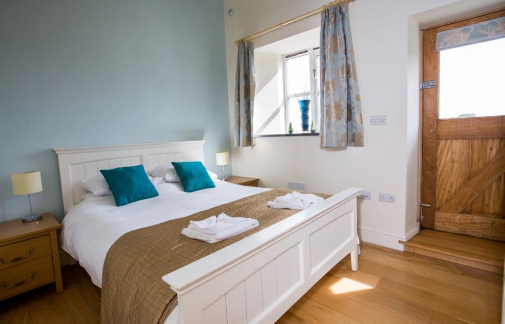 This image is of the double bedroom in cottage number four. The room has oak flooring the wall behind the bed is painted pale blue. There are two oak bedside tables one on each side of the bed. Each has two drawers. On each bedside table there is a stainless steel bedside light with a cream shade. The bed is made of wood and is painted white. The bed linen is white there are four pillows two on each side. On each set of pillows there is a teal cushion. At the base of the bed there is a folded gold throw. On this throw there are two sets of folded white towels. The wall right of the bed is painted cream in on this wall there is a door and a window. The window is a four pane casement style window there is a slate windowsill. On the slate windows ill there is a blue vase. The curtains are pale blue with a gold floral design. The door leads to the outside. The door is a half glazed door there is a blind with the same fabric as the curtains on the glazed section of the door. The door is made of oak. There is a step from the floor level to exit the door.
