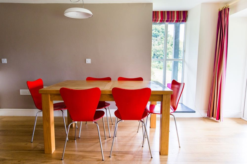 This image is of the dining area of cottage number five. Cottage number five sleeps six people. The image shows a rectangular dining table which is made of oak. Around the table there are six red dining chairs. The floor is made of oak. The wall behind the table is painted at taupe colour. There is a white bowl shaped pendant light above the table. To the right of the table there is a large full height four pane casement window. This window goes from ceiling to floor. There is a slate windowsill. There is a striped blind in red cream and brown tones. In the wall to the right of the photo there is another window you can see a full length curtains in this window made of the same fabric as the blind.